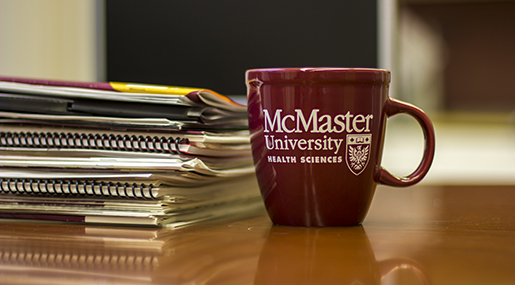 A picture of evidence briefs on a table with a McMaster coffee mug.