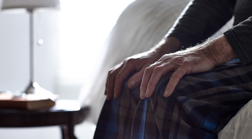 Elderly hands placed on knees to symbolize joint pain